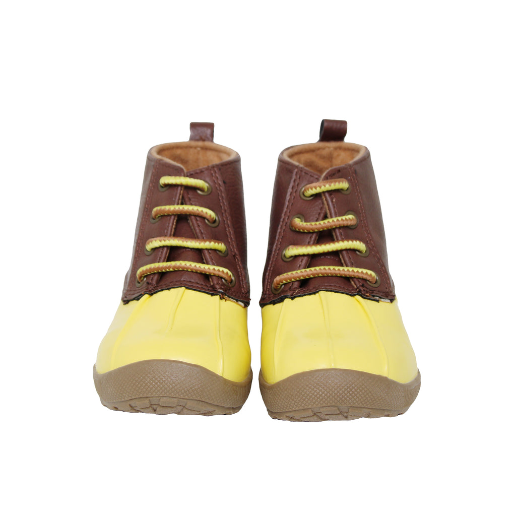 Front view of baby toddler rain boots with patent leather shoe tops and bright yellow rubber water proof bottoms and soles
