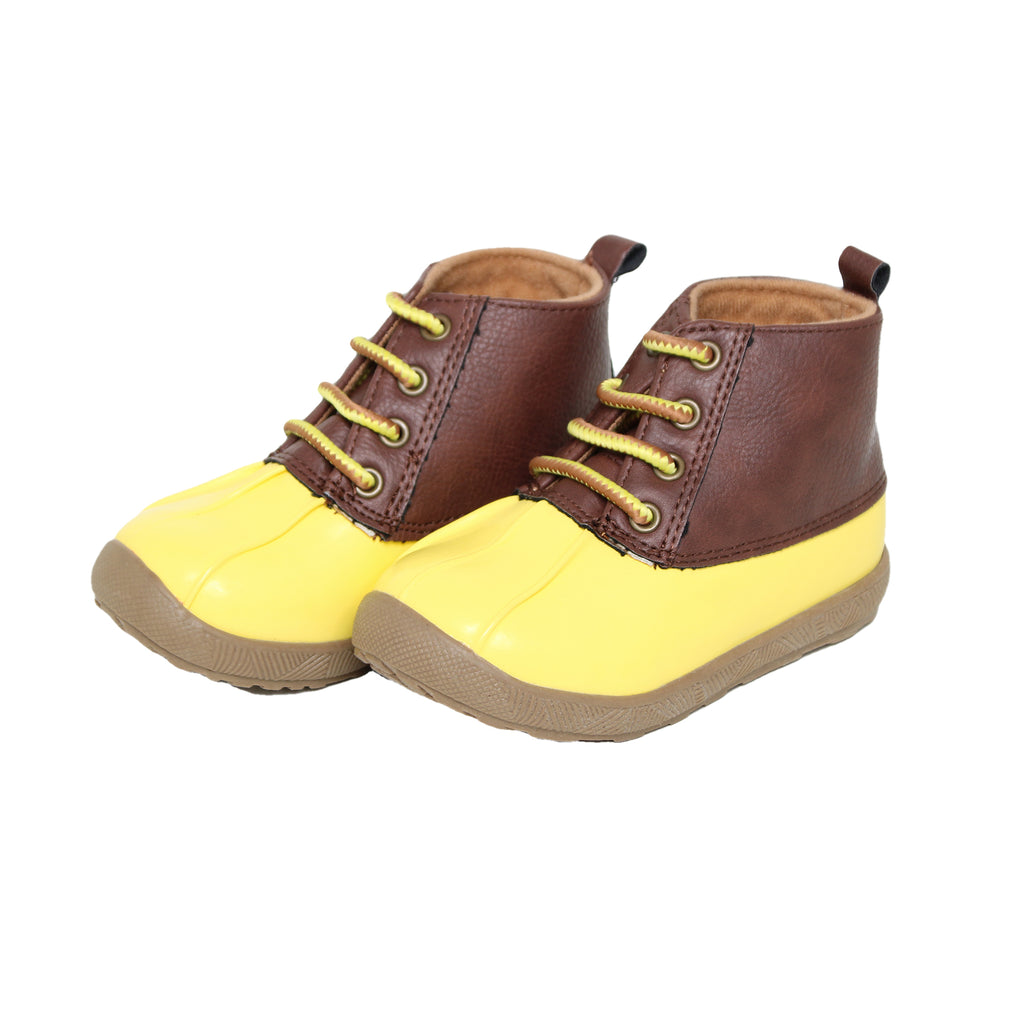 Side view of baby toddler rain boots with patent leather shoe tops and bright yellow rubber water proof bottoms and soles