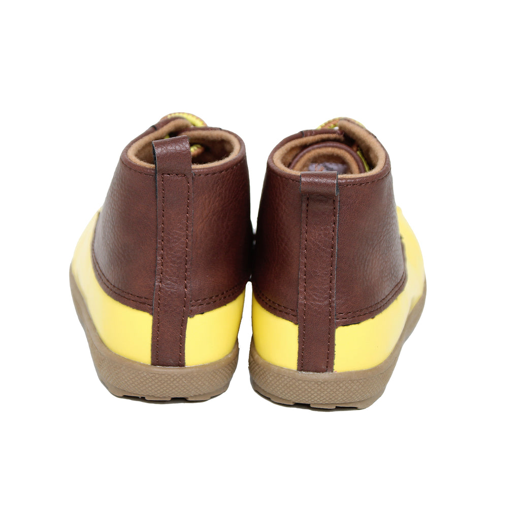 Back view of baby toddler rain boots with patent leather shoe tops and bright yellow rubber water proof bottoms and soles