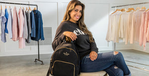 Woman wearing black chic sweatshirt, sitting on a chair next to a black Kate Spade backpack.