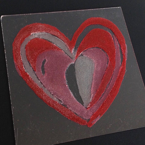 red and pink colored sand heart painting