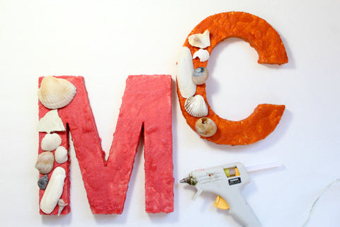Hot glue seashells to a wood letter painted with colored sand.
