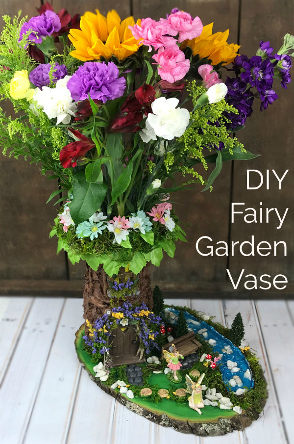 GORGEOUS!  Learn how to make a DIY fairy garden vase with a plain florist's vase!  This project tutorial shows you how to create this stunning fairy garden scene.  It's easier than you might think!