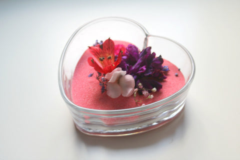 A dollar store glass bowl filled with colored sand and dried flowers makes a great DIY wedding centerpiece!