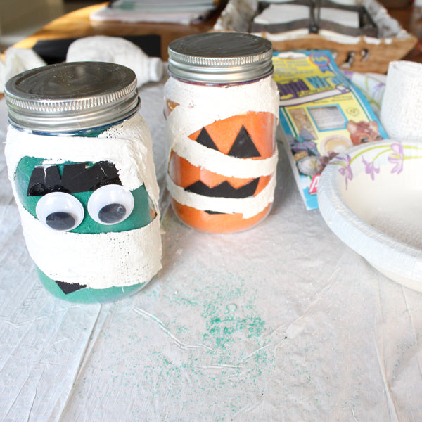 Create adorable mummy mason jar candleholders for Halloween with Rigid Wrap plaster cloth and Scenic Sand colored sand!