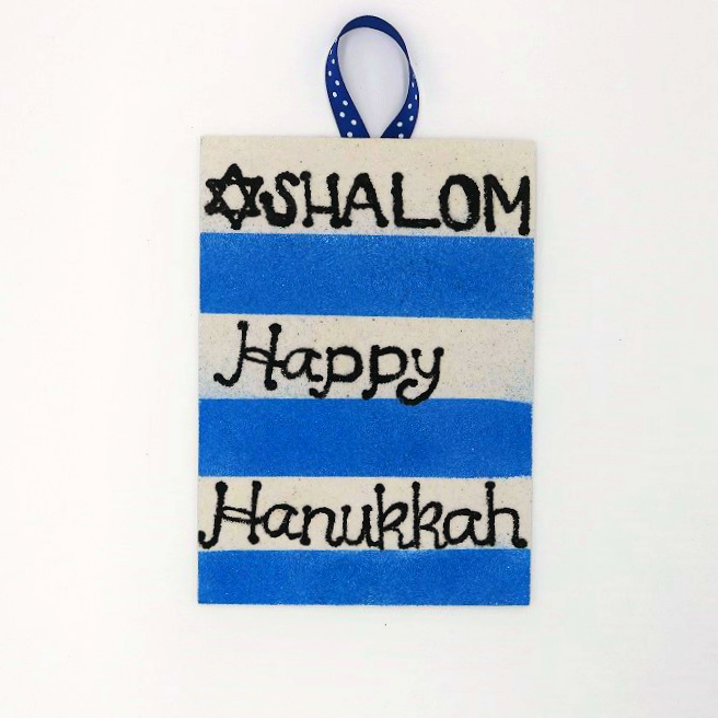 Create pretty Hanukkah wall art with colored sand and blank adhesive boards.