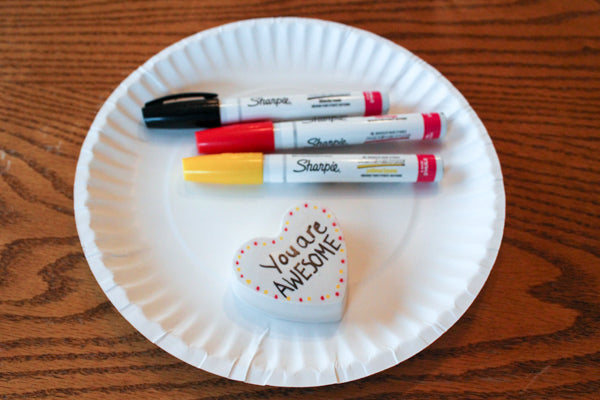 Decorate heart-shaped kindness rocks with oil-paint markers.