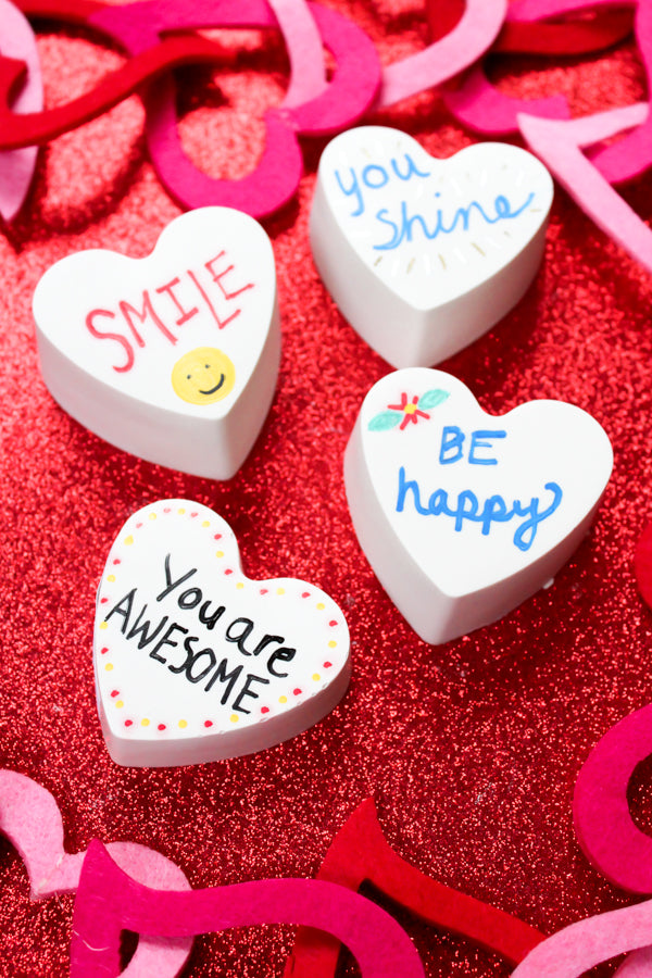 Create heart-shaped kindness rocks with this fun tutorial!  It's so easy to make heart shaped rocks.  They're perfect for Valentine's Day or any day!  #kindnessrocks  #Valentine #kidscrafts