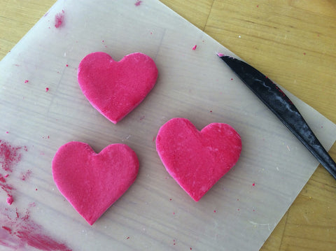 Making air dry clay Sacred Heart magnets is fun.