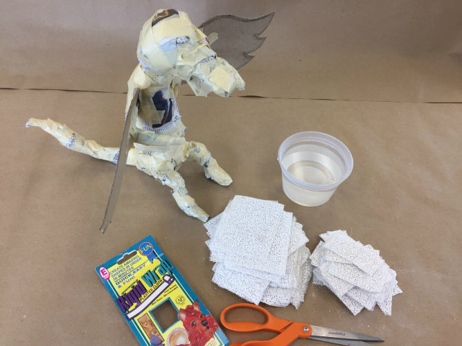 The third step of creating a dragon with Rigid Wrap plaster cloth is to cut Rigid Wrap into smaller pieces.