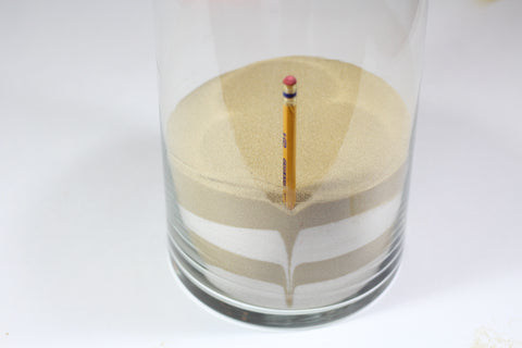 Use a pencil to push the sand down around the edge of the vase in order to create patterns.