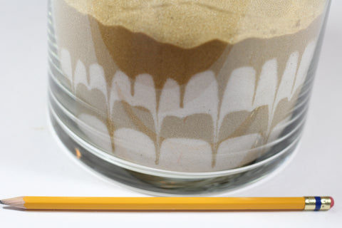 Push the pencil around the outer edge of the vase to create patterns in the sand.