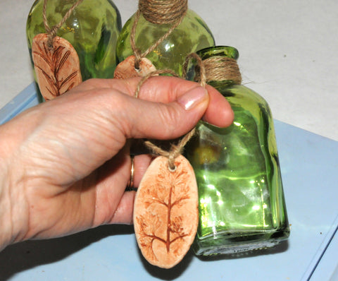 hang clay pendant on herb bottle