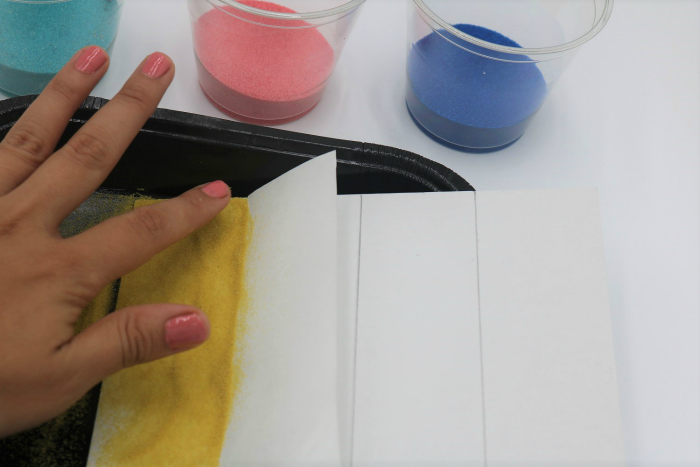 It's easy to create colored sand art with adhesive or sticky boards.