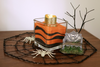 Create a Halloween colored sand candle arrangement with orange colored craft sand and black colored craft sand.