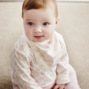 baby girl wearing pink long sleeved top
