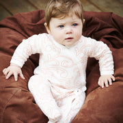 baby girl wearing shmuncki cotton baby grow in a swirl pattern print