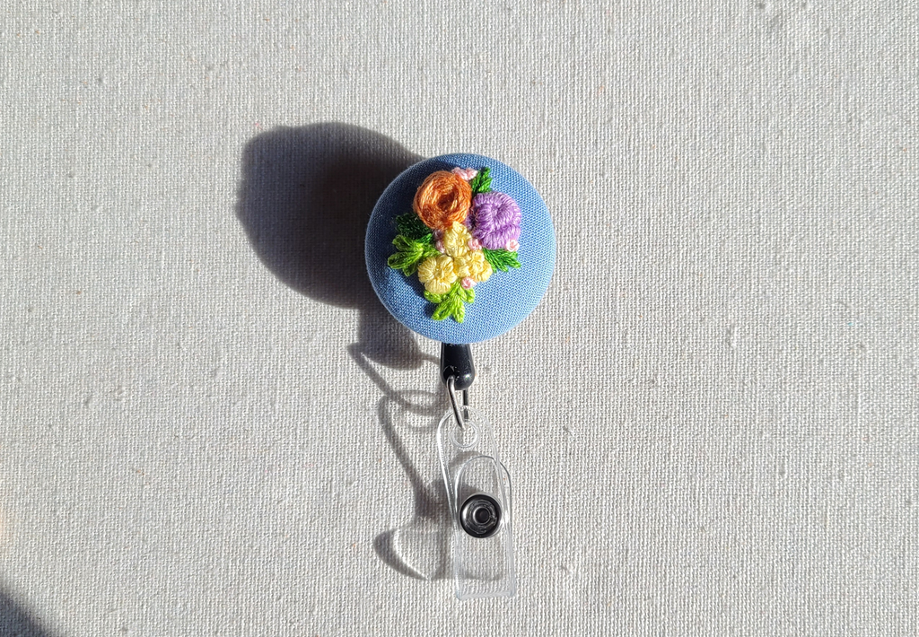 Orange and Lemon Yellow Flowers on Light Blue Retractable Badge Reel