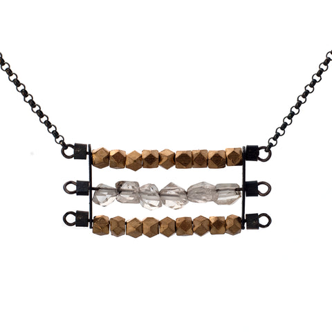 "Abacus necklace with two rows of faceted brass beads and one row of clear Herkimer Diamonds, suspended horizontally on black oxidized sterling silver rungs, hanging from a black oxidized sterling silver chain.  Approximately 17"" in length."