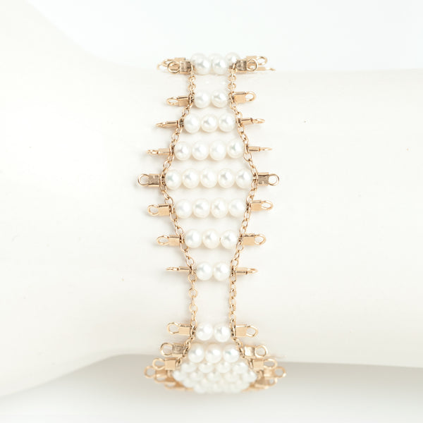 Kellan bracelet, featuring undulating rows of lustrous, white pearls, suspended on rows of 14k gold-fill wire and chain, and finished with a lobster clasp.  Approximately 7 inches in length.
