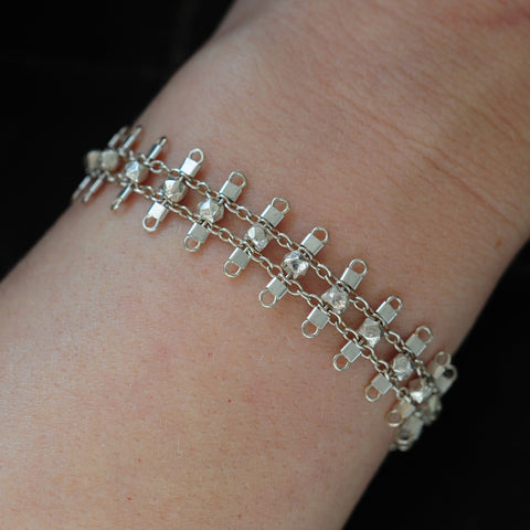 Artemis bracelet, featuring faceted, sterling silver beads suspended on sterling rungs and chain, finished with a lobster clasp.  Approximately 7 inches in length.