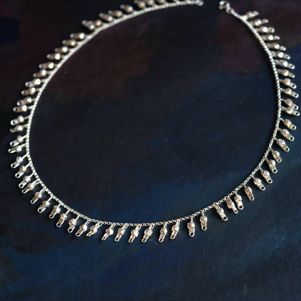 A sterling silver fringe-style necklace of silver faceted beads dangling off a silver chain all the way around.
