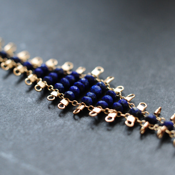 Juda bracelet, featuring faceted, navy blue, lapis lazuli beads suspended on 14k gold-fill wire and chain, finished with a lobster clasp.  Approximately 7 inches in length.