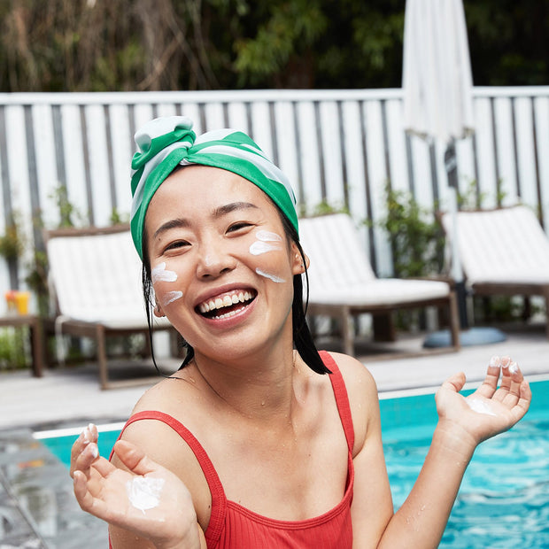Sun protective hair wrap paired with suncreen in pool