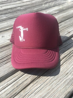 Adjustable, lightweight, Lazy Dog Brand Maroon Foam Trucker Hat with white screen printed paddle board girl and dog offset on left side of hat when looking at hat.