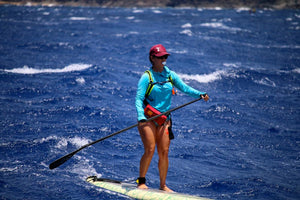 Female Paddler wearing an Adjustable, lightweight, Lazy Dog Brand Maroon Foam Trucker Hat with white screen printed paddle board girl and dog offset on left side of hat when looking at hat.