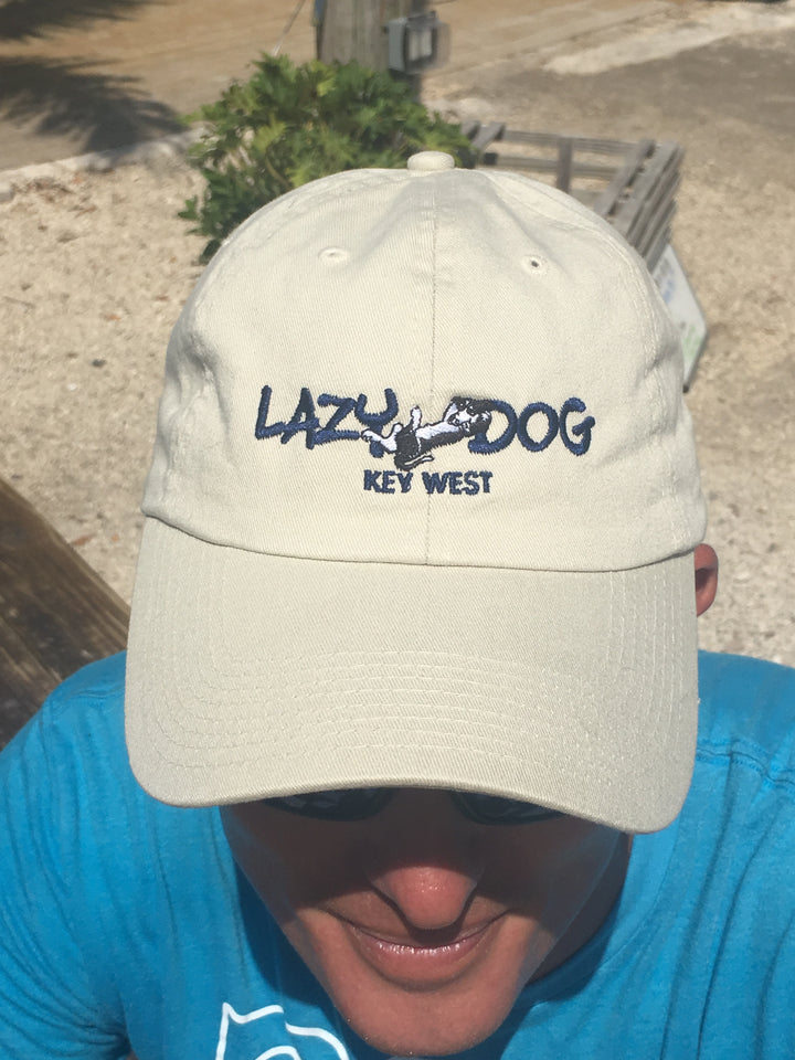 "Lazy Dog Brand All Cotton, Adjustable Ball cap with navy lettering ""Lazy Dog"" and a lounging black and white border collie embroidered in center of hat. Natural"