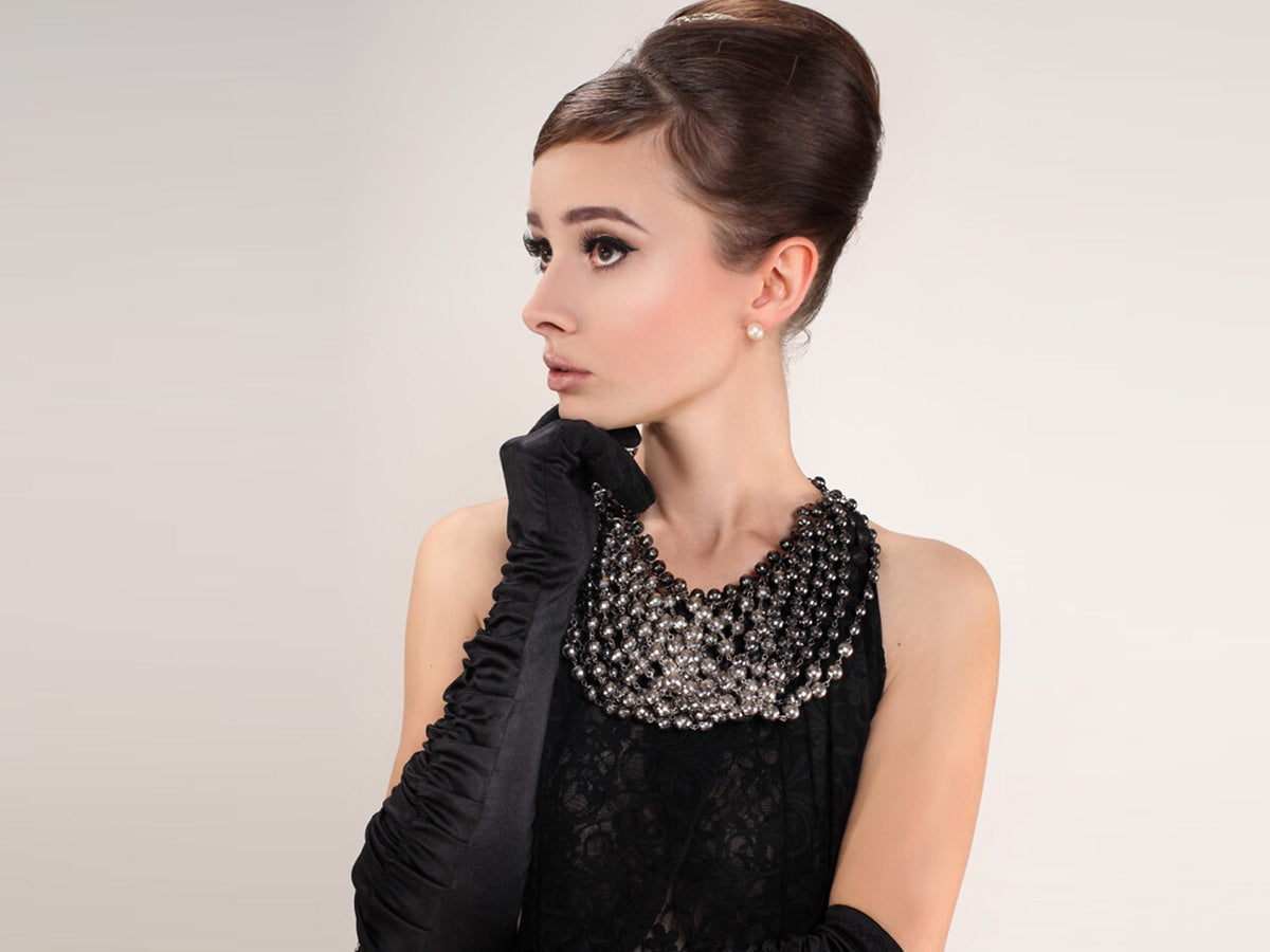 Woman who looks like Audrey Hepburn with pearl necklace