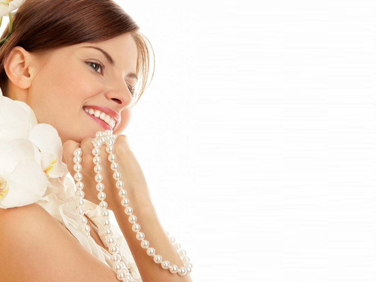 A pretty young woman clutching a pearl necklace and smiling