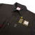Front detail shot of Men's Dual Shirt in Black showing wallet in chest pocket, button detail, and logo patch.