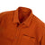 Detail shot of Topo Designs Men's Dirt Shirt in Brick orange showing collar, inside tag, buttons, and chest pocket.