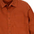 Detail shot of Topo Designs Men's Dirt Shirt in Brick orange showing buttons and chest pocket.
