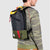 3/4 back model shot of Topo Designs x Alternative Trip Pack in olive/black showing backpack carry style