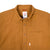 Detail shot of Topo Designs Men's Route Shirt in Khaki brown showing collar, front buttons, and chest pocket.