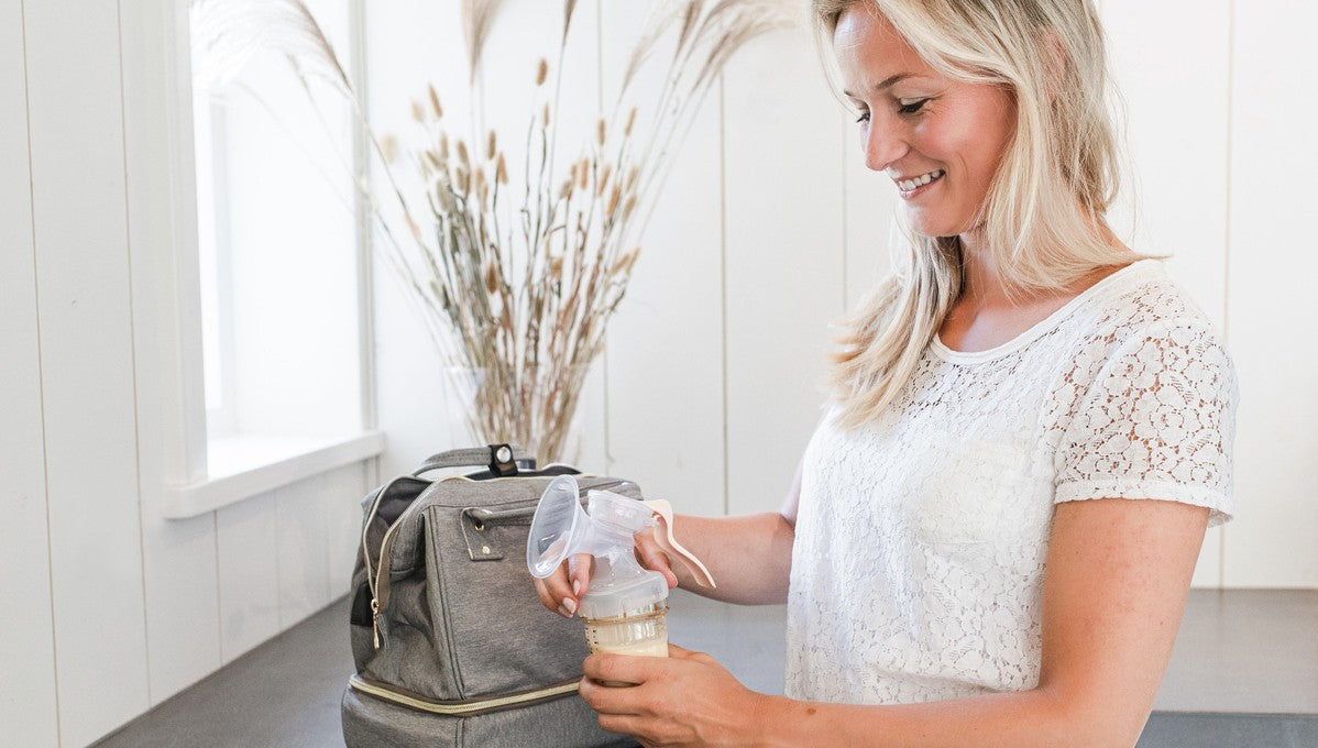 Woman putting manual breast pump attachment on bottle