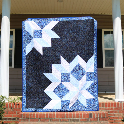 Water Crystals quilt on the front steps of a house between columns, long are quilting by Stitched in Purple