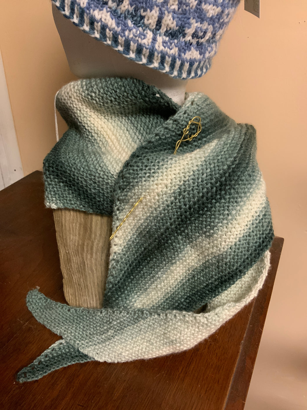 Shades of green and cream hand-knit shawl, with brass pin