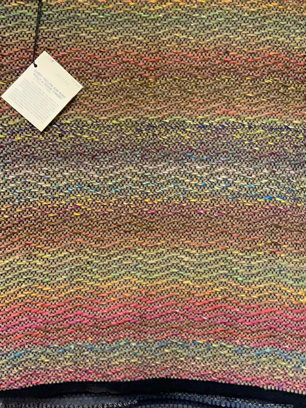 "Brown and multicolored wool yarn woven in a wave pattern.  Rug is 28"" x 43"""