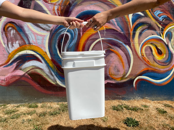 Bucket Being Passed in Front of Colourful Wall