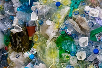 A picture of a landfill full of plastic bottles and other trash
