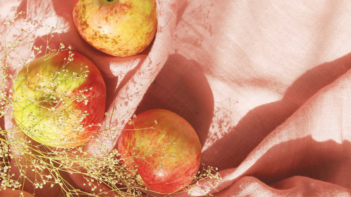 Three apples lay on a light pink linen cloth.