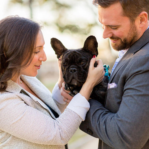 A man and a woman embrace a french bulldog while smiling at the dog