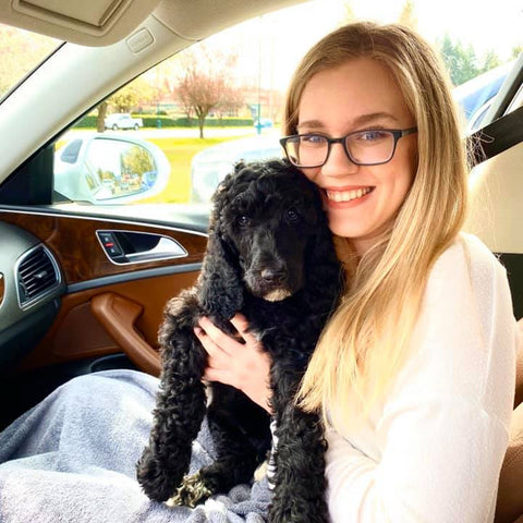 A woman sits in a car passenger seat, holding a poodle puppy and smiling