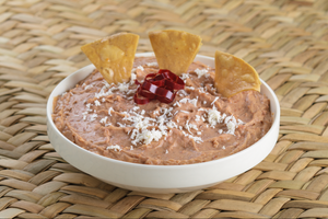Bowl of Green Roots Meals authentic Mexican refried pinto beans topped with queso fresco and chips