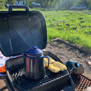 Corn tamales warming up next to a kettle on a camp stove