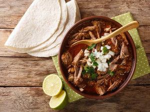 Bowl of authentic Barbacoa Jalisco with flour tortillas and lime on the side